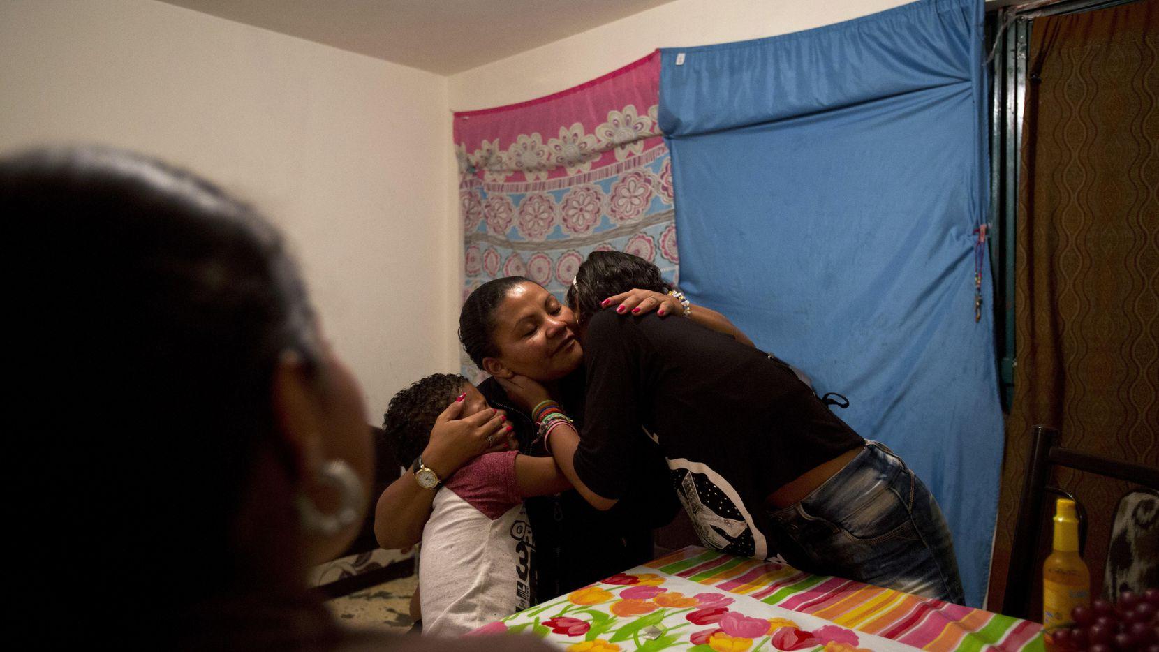 La refugiada hondureña Laura María Cruz Martínez recibe un abrazo de sus hijos Ruth, de 12 años, y Josué, de siete, tras llorar al escuchar una canción que agradece a una madre soltera por la fortaleza con la que ha educado a sus hijos. Cruz se encarga de sus tres hijos sola y también es una madre para que su sobrina adolescente. La mujer huyó de Honduras junto con otra madre soltera y nueve niños después de recibir amenazas de pandilleros (AP/REBECCA BLACKWELL)