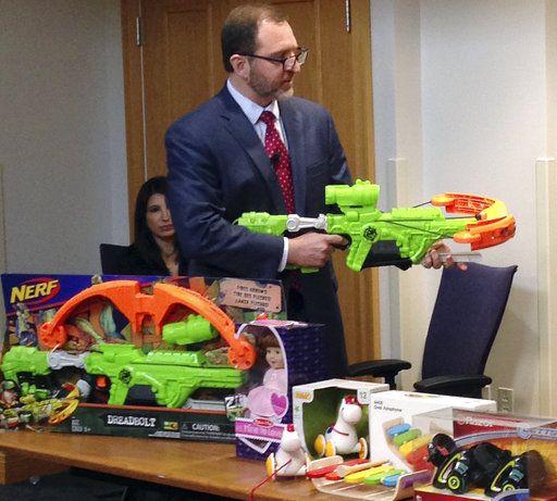 """James Swartz, director de WATCH, una organización que revisa la seguridad de los juguetes, muestra la ballesta """"Zombie Strike"""" de Nerf, en Boston, el 14 de noviembre de 2017. El grupo presentó su lista de los juguetes más peligrosos para los niños. (AP Foto/Philip Marcelo)"""