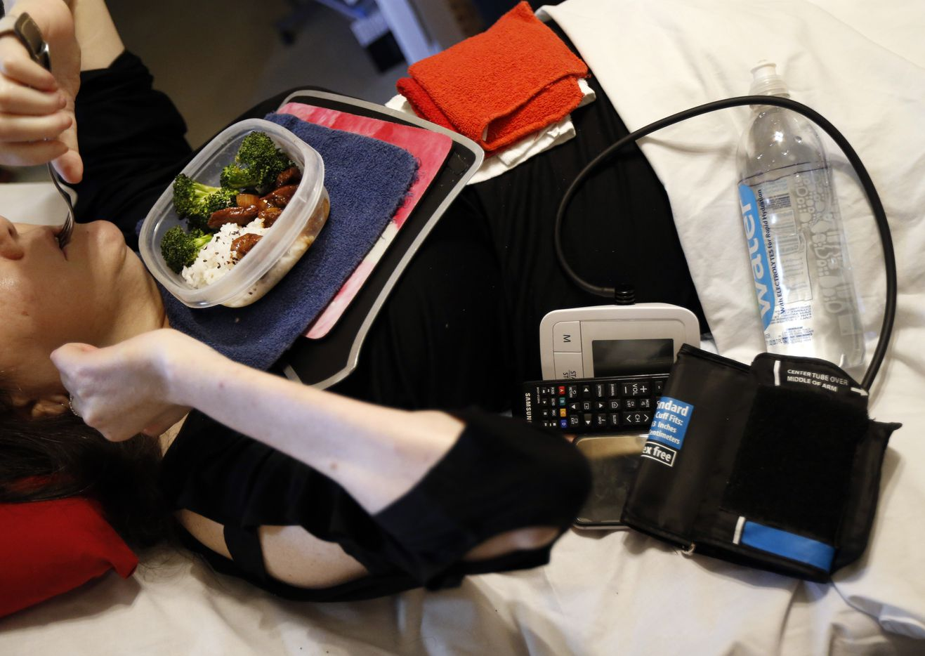 Since Powell can't get out of bed, she eats her meals there, while keeping her blood pressure machine, a bottle of water, phone and remote controls close by.