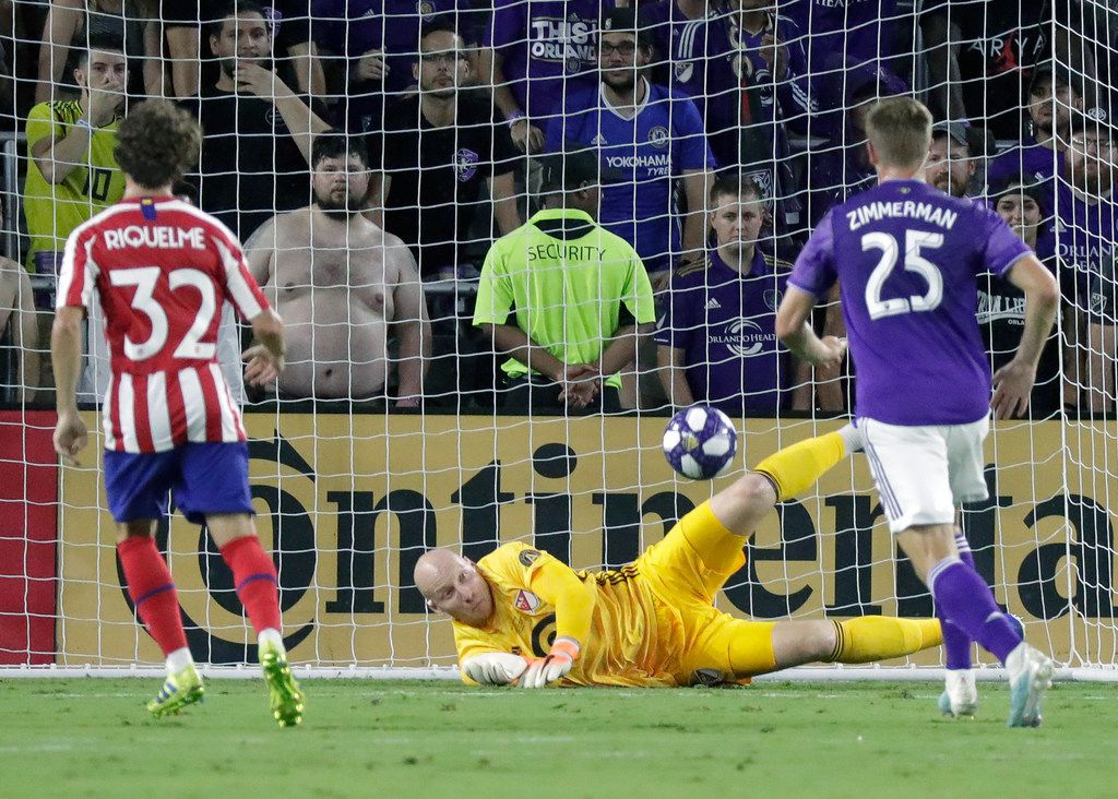Atlanta United goalkeeper Brad Guzan, center, blocks a shot by Atletico Madrid midfielder Rodrigo Riquelme (32) as Los Angeles FC defender Walker Zimmerman (25) comes in to assist during the first half of the MLS All-Star soccer match Wednesday, July 31, 2019, in Orlando, Fla. (AP Photo/John Raoux)