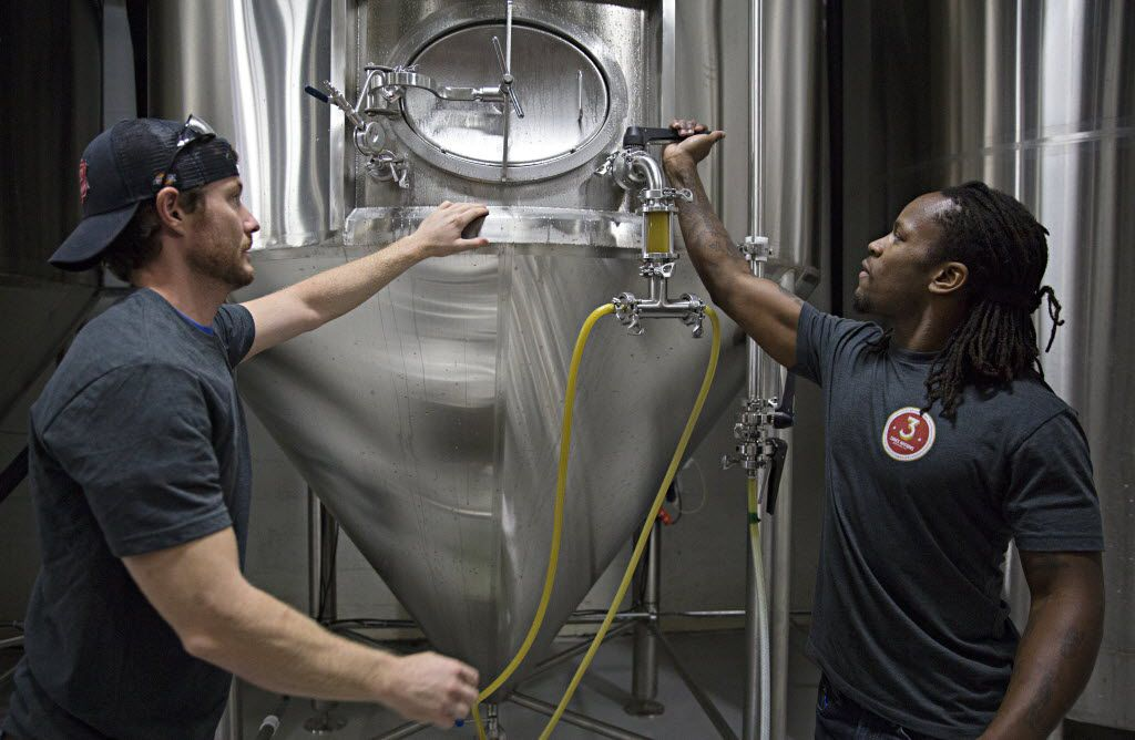 Gavin Secchi (left) and Steven Aikens prepare to fill kegs at 3 Nations Brewing.
