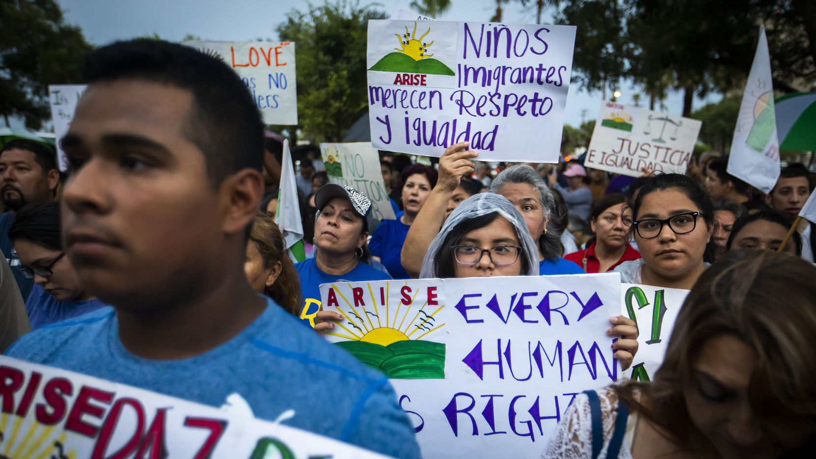 People hold signs in support of immigrants during an interfaith prayer vigil and walk for migrant families.