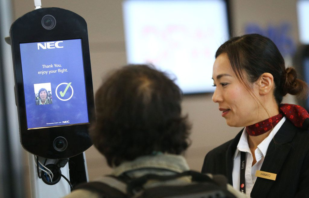 Hanayo Yoon, a customer service agent with Japan Airlines, helps a passenger use new biometric facial scanning technology before boarding a flight to Tokyo in Terminal D at Dallas/Fort Worth International Airport in Irving, Texas on Tuesday, Nov. 20, 2018.
