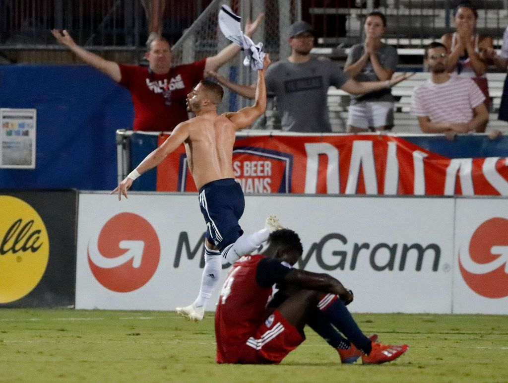 FC Dallas' Dominique Badji sits on the field as Vancouver Whitecaps' Lucas Venuto removes his shirt, celebrating his goal in the second half of an MLS soccer match in Frisco, Texas, Wednesday, June 26, 2019. Venuto was issued a yellow card for removing the jersey in the 2-2 tie. (AP Photo/Tony Gutierrez)