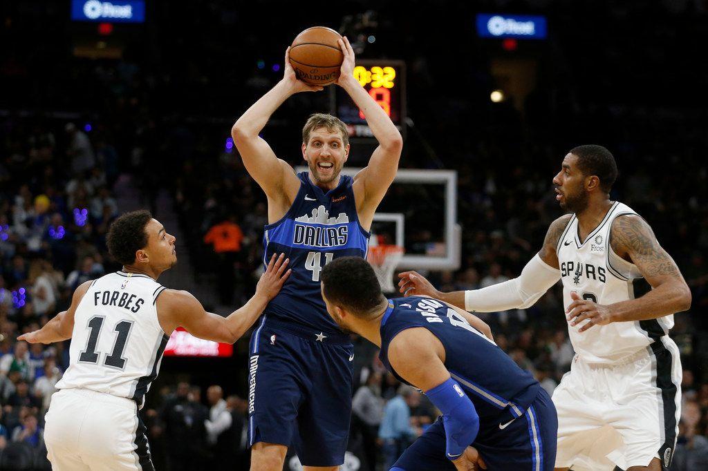Dallas Mavericks forward Dirk Nowitzki (41) passes to teammate Jalen Brunson (13) between San Antonio Spurs guard Bryn Forbes (11) and San Antonio Spurs center LaMarcus Aldridge (12) during the second half of play at AT&T Center in San Antonio, Texas on Wednesday, April 10, 2019. (Vernon Bryant/The Dallas Morning News)