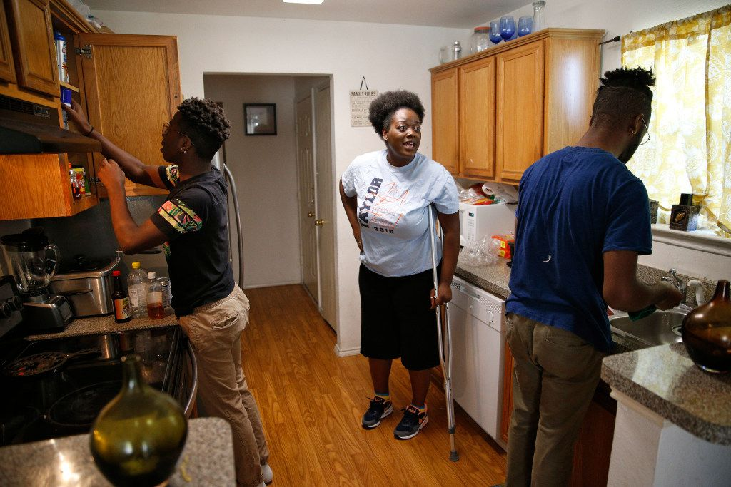 Shetamia Taylor teaches her sons Jajuan Washington, 15, and Kavion Washington to prepare their Thanksgiving meal at her Garland home on Nov. 23, 2016. She is recovering from being shot by a sniper in the downtown Dallas ambush.