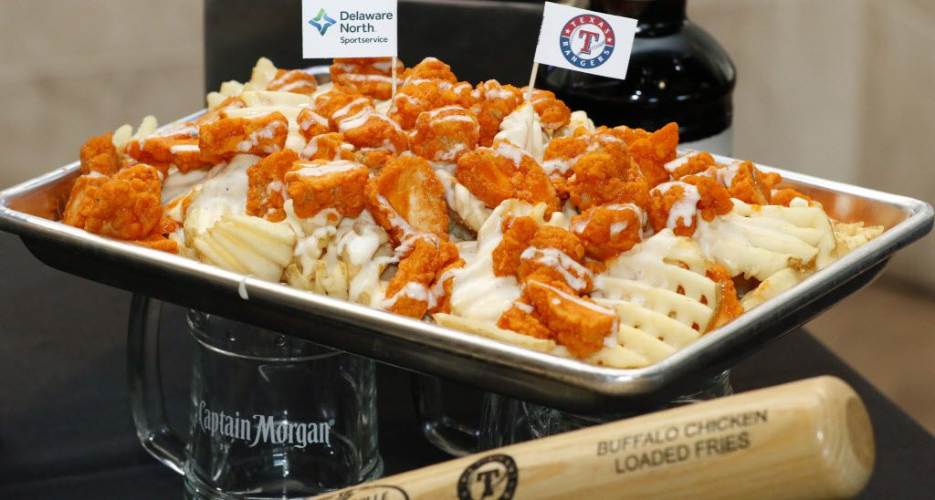 The Buffalo Chicken Loaded Fries are waffle fries topped with buffalo chicken and white queso, served with a side of ranch dressing. Located in the Captain Morgan Club.