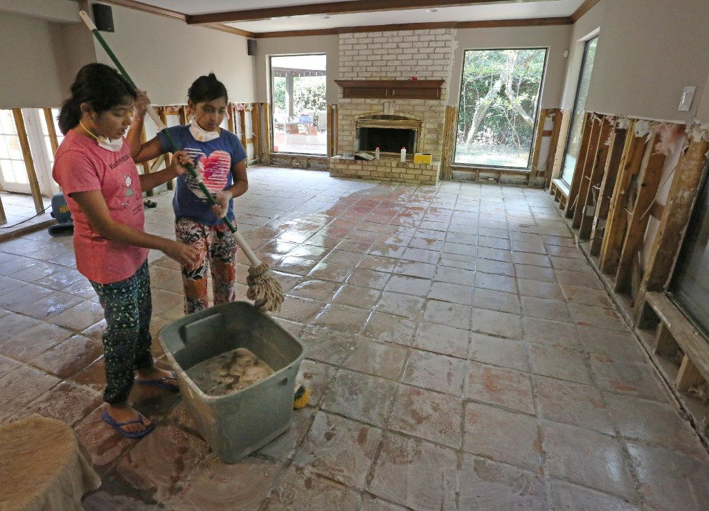 Twin sisters Saloni and Sugani Singh, 10, share mopping duties as they work to clean up their home in the Memorial Drive Acres subdivision, which was flooded as a result of water released from the Army Corps of Engineers' dams upstream.