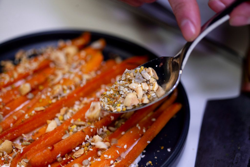 Chef Matt McCallister prepares glazed carrots with creme fraiche and seeded crumble in The Dallas Morning News' test kitchen on Dec. 18, 2018.