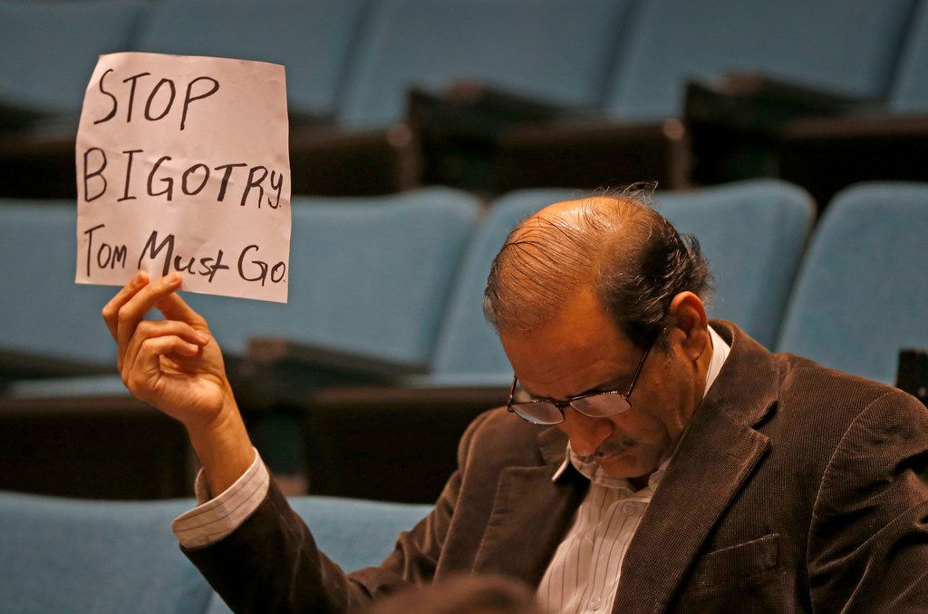 Plano resident Hasan Waqar holds up a sign while Mayor Harry LaRosiliere speaks during a news conference at Plano Municipal Center on Feb. 14, 2018. The mayor called for immediate resignation of City Council member Tom Harrison, who shared an anti-Islamic post on his Facebook page.