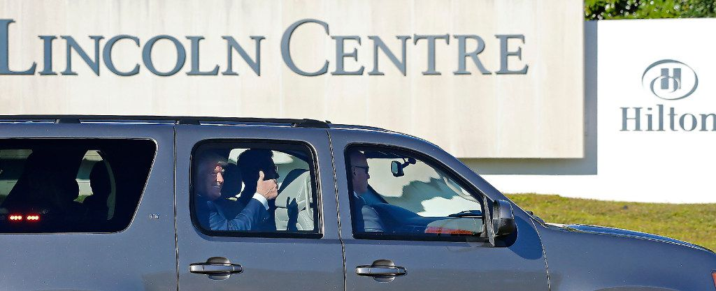 Republican presidential candidate Donald Trump gives his supporters a thumbs up in the motorcade leaving the Lincoln Centre after a fundraising event in Dallas, Tuesday, Oct. 11, 2016.