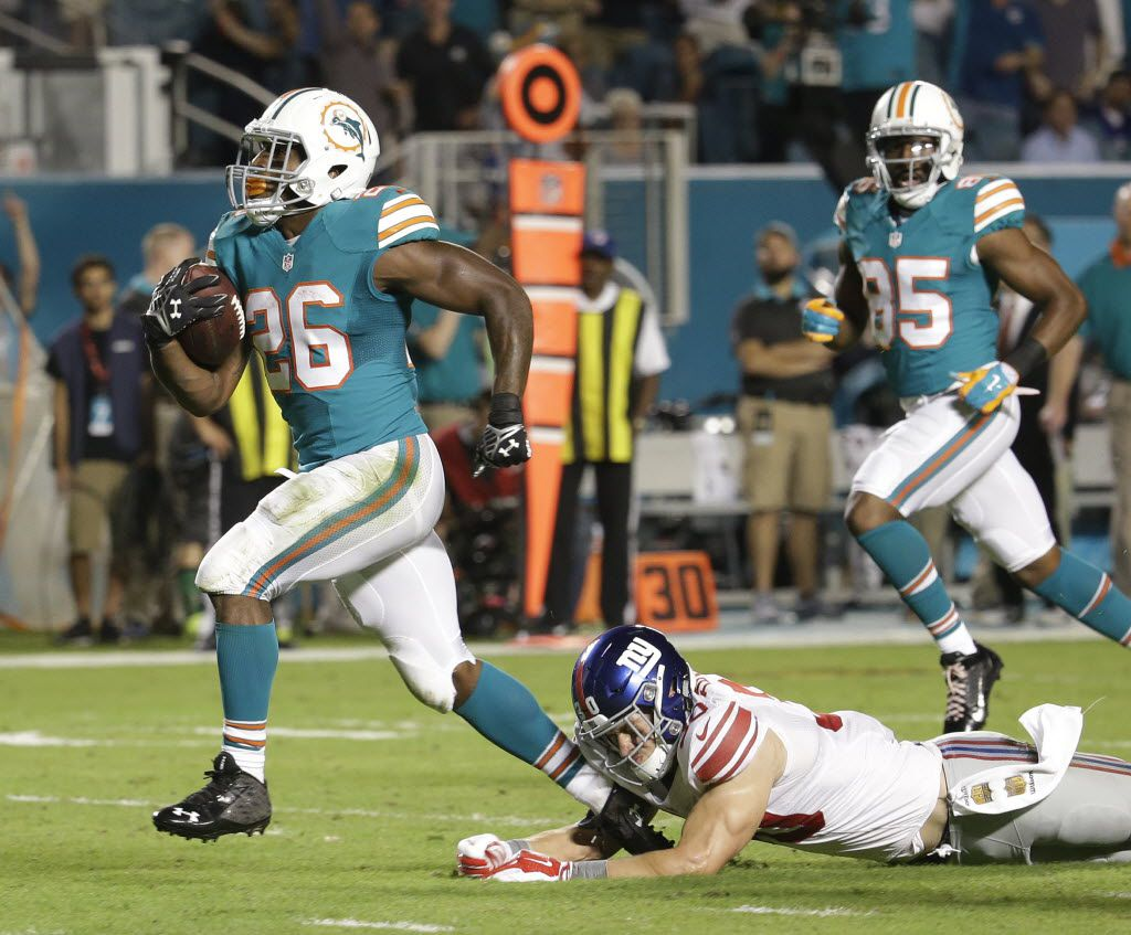 Miami Dolphins running back Lamar Miller (26) breaks a tackle by New York Giants defensive back Cooper Taylor (30) and runs for a touchdown, during the first half of an NFL football game, Monday, Dec. 14, 2015, in Miami Gardens, Fla.  (AP Photo/Lynne Sladky)