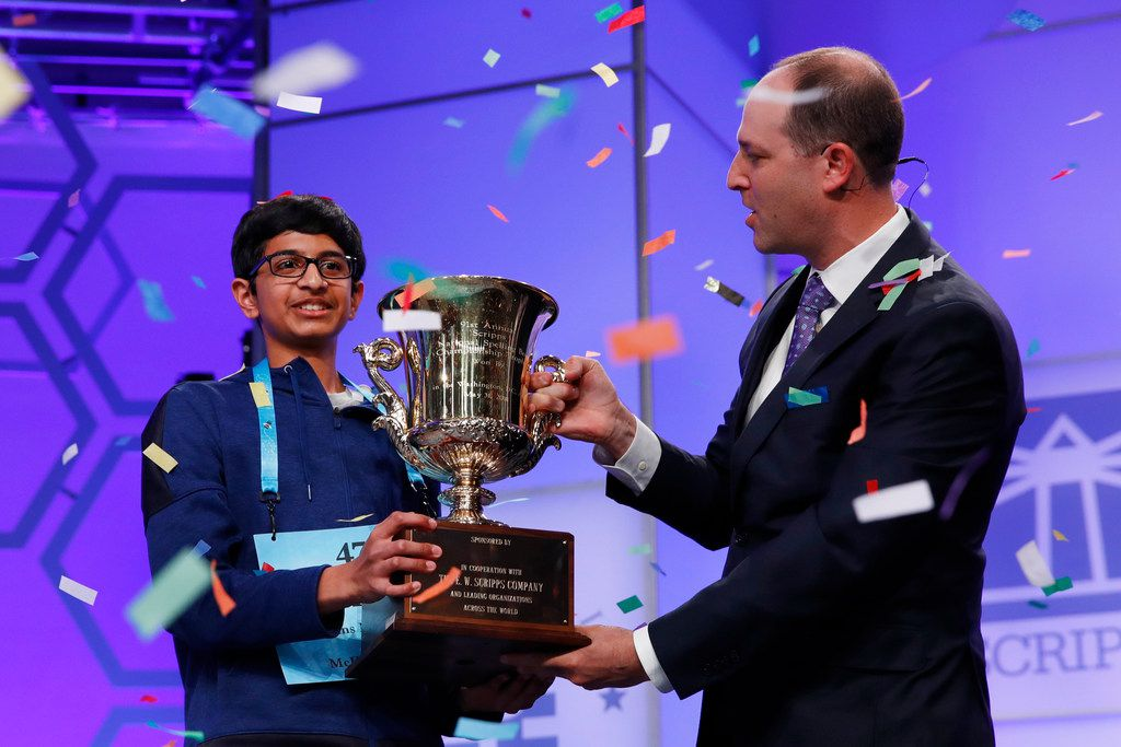 Karthik Nemmani, 14, from McKinney, Texas, left, holds his trophy with President and CEO of the E.W. Scripps Company Adam Symson as confetti falls after winning the Scripps National Spelling Bee in Oxon Hill, Md., Thursday, May 31, 2018.  (AP Photo/Jacquelyn Martin)