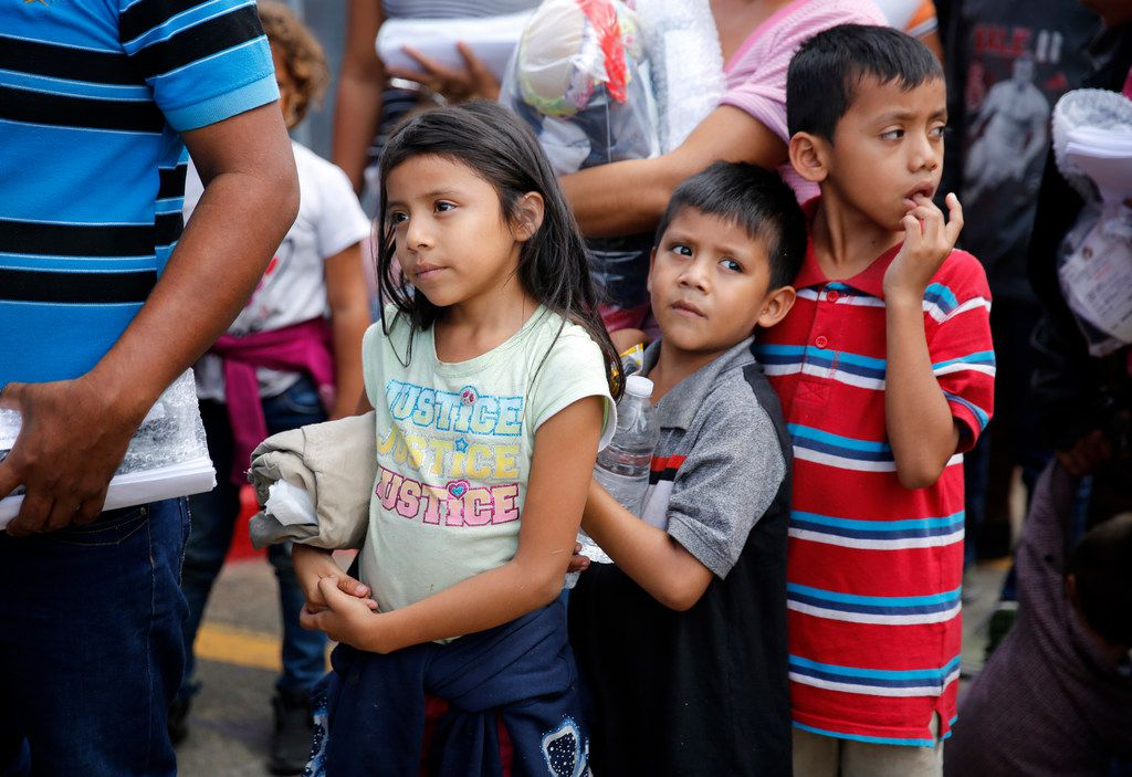 Immigrant children fleeing Central America arrive on government buses at the Central Station bus terminal in downtown McAllen on Sunday, June 24, after being processed by the U.S. Border Patrol.  From there the families were gathered up and walked a few blocks away to the Catholic Charities of the Rio Grande Valley. There they can get cleaned up, fed and receive help getting transportation to their future destinations. (Tom Fox/The Dallas Morning News)