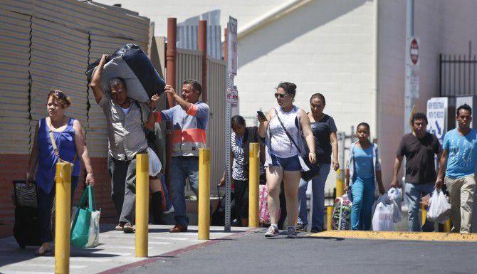 Un grupo de peatones se alista para cruzar de San Diego a Tijuana. Autoridades han creado dos líneas, una para mexicanos, y la otra para extranjeros que deben mostrar pasaporte antes de entrar a a México. (AP/LENNY IGNELZI)