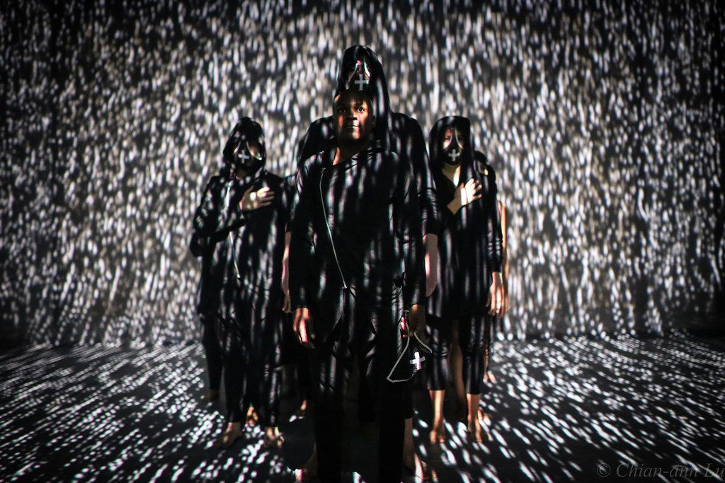 The performers in Charles O. Anderson's (Re)current Unrest are often drenched in projected imagery.