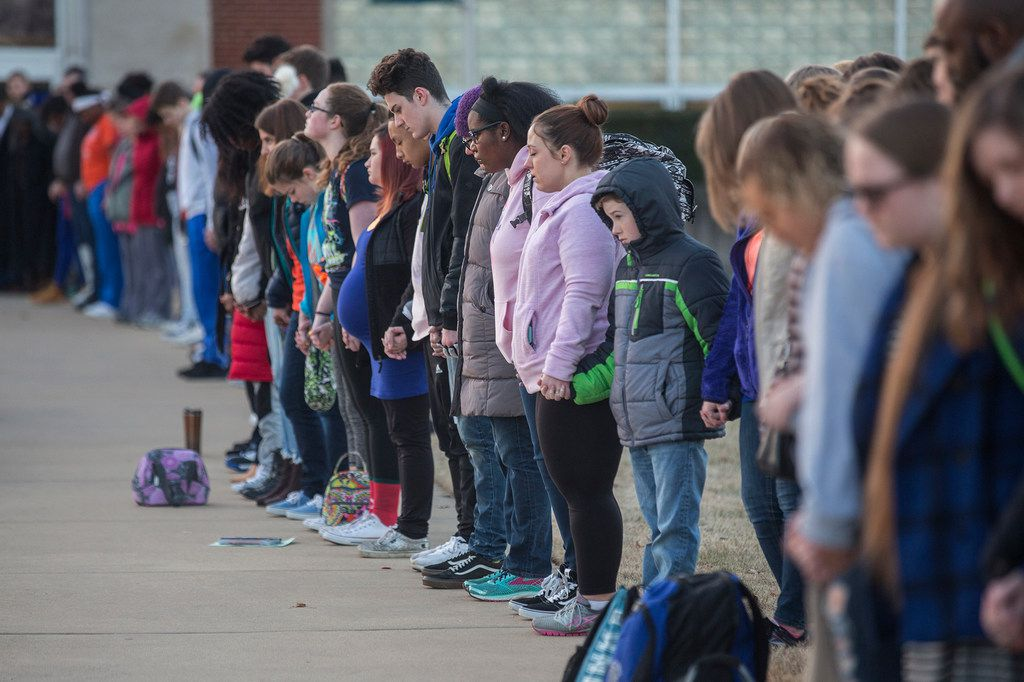 Students and community members hold hands in prayer before classes at Paducah Tilghman High School in Paducah, Ky., on Wednesday. The gathering was held for the victims of the Marshall County High School shooting on Tuesday.