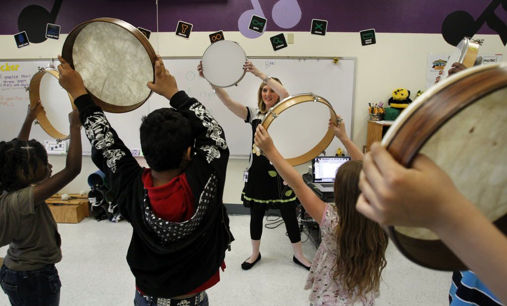Karen Becker (center) uses tambourines in a mirroring exercise in her third-grade music class at Garner Fine Arts Academy in Grand Prairie. the campus is located near housing for GPISD Superintendent Susan Simpson Hull.