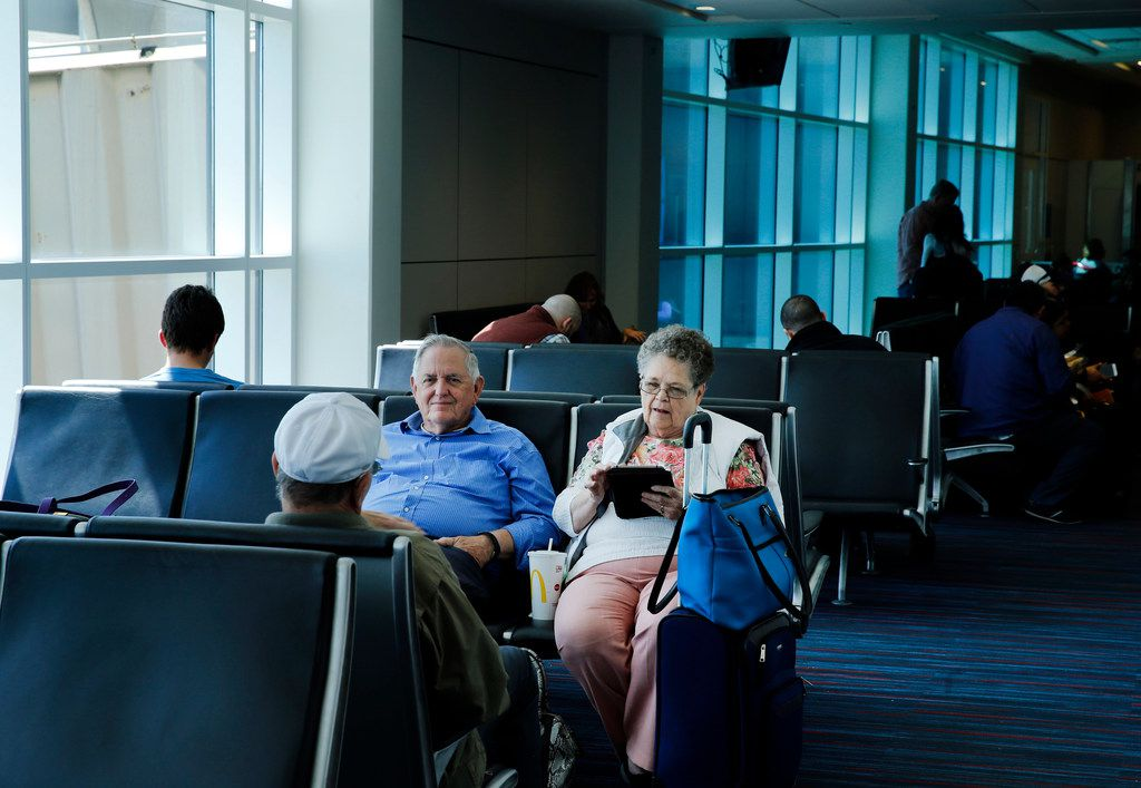 Passengers wait to board their flight in an areas with the current windows and unshaded sunlight in Terminal A at Dallas-Fort Worth International Airport, Monday, April 16, 2018. DFW Airport is testing new window technology View Dynamic Glass that varies the opacity of panes to let in less light (background), making seating areas cooler and more comfortable while also cutting the airportÕs cooling costs. One of the gates in Terminal A and a burger joint have the electrically charged blue-tinted windows installed. (Tom Fox/The Dallas Morning News)