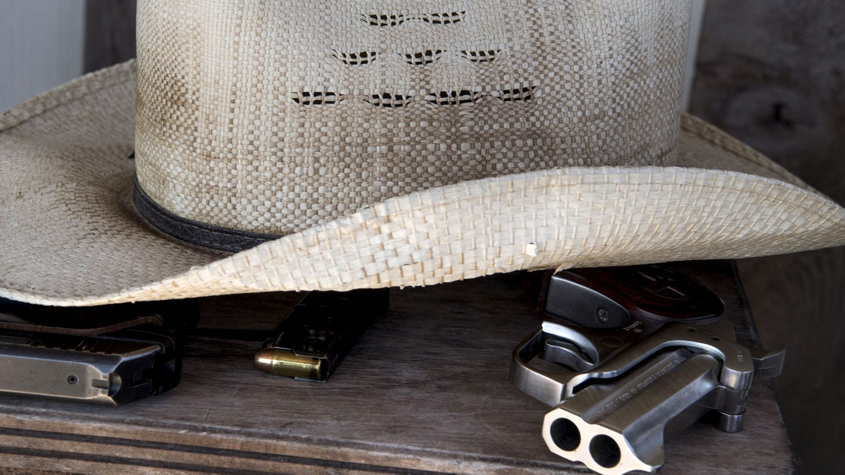 Two of Kevin Langdon's guns sit under his hat at his home in Sutherland Springs, Texas.