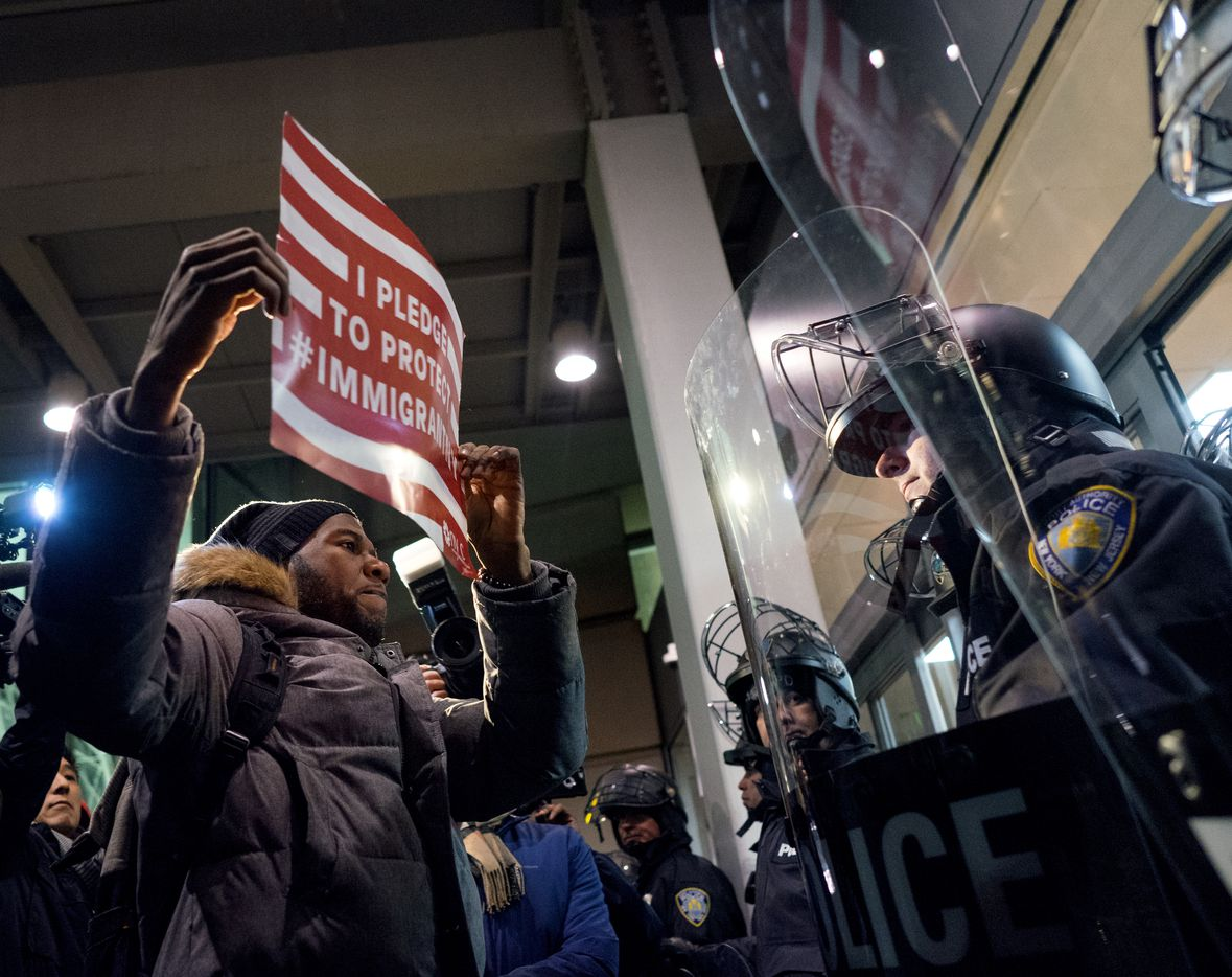 A protester stands facing police officers at an entrance of Terminal 4 at John F. Kennedy International Airport in New York, Saturday, Jan. 28, 2017,  after earlier in the day two Iraqi refugees were detained while trying to enter the country.