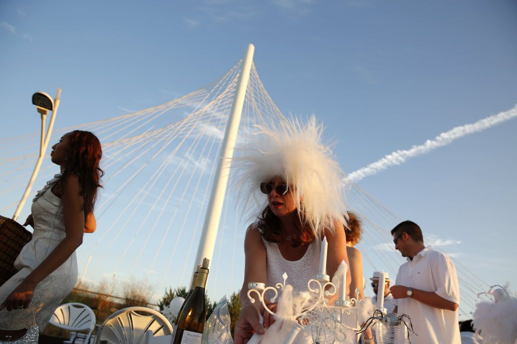 Carol Calderbank sets up a centerpiece during the inaugural Diner en Blanc Dallas on the Continental Avenue Bridge in Dallas on Sept. 17, 2015. Exactly 1,678 people attended the event, which requires dinner guests to dress all in white and bring their own tables, chairs and centerpieces. As per tradition, the location was kept private leading up to the event.