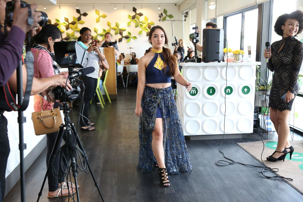 Daniella Hinojosa models a Celeste Johnson design, as Celeste Jonson speaks at the fashion show event, at right, at Asian Mint benefiting Genesis Women's Shelter in Dallas on June 4.