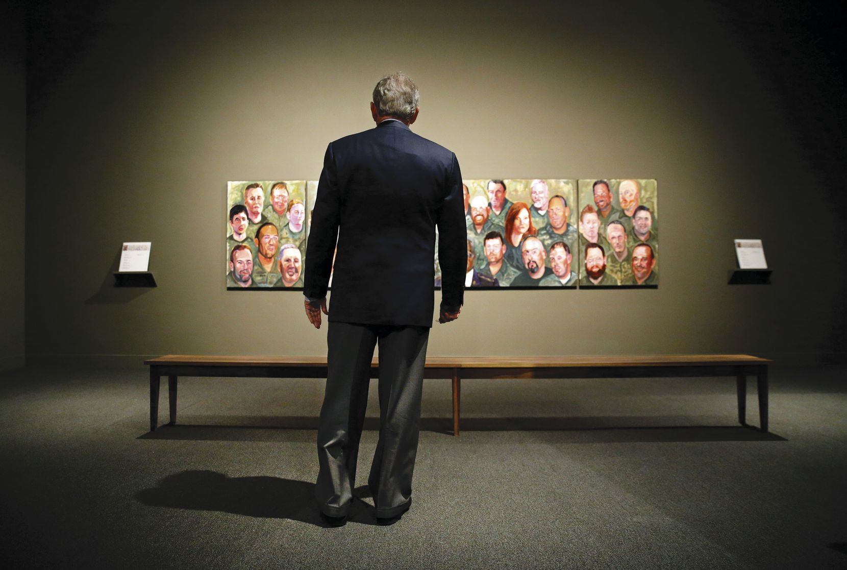 "Former President George W. Bush views his ""Portraits of Courage, a Commander in Chief's Tribute to America's Warriors"" exhibit for the first time at the George W. Bush Presidential Center. It included the four-panel mural shown here and 66 portraits of U.S. military members who've served with honor since 9/11 — and whom Bush has come to know personally."