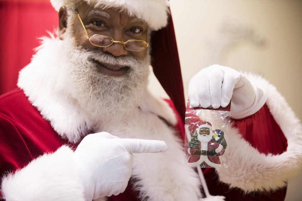 """Santa Larry Jefferson holds up some """"multicultural"""" Santa merchandise for sale at the Santa Experience at Mall of America on Dec. 1, 2016 in Bloomington, Minn."""