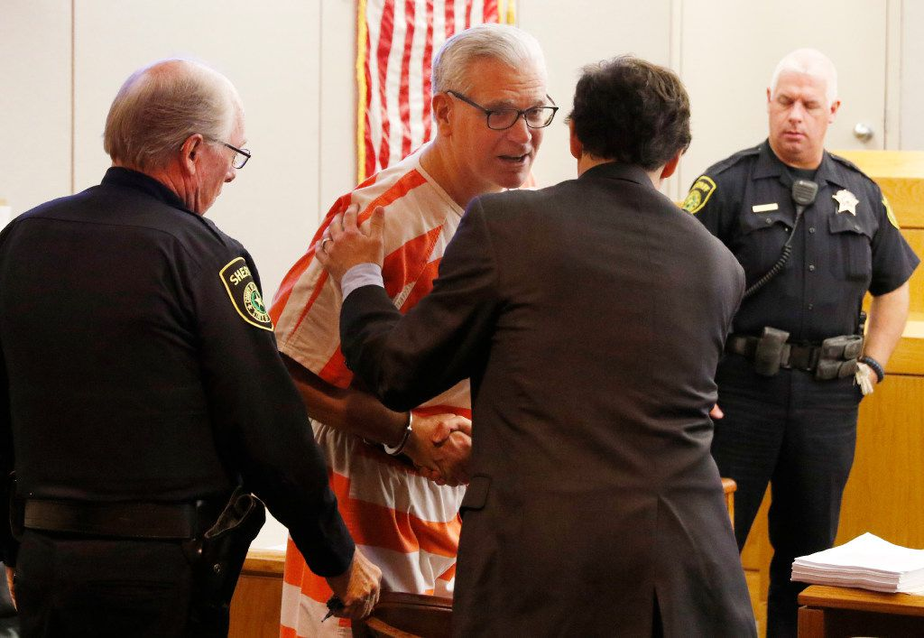 John Battaglia, second from left, greets his attorney, Greg Gardner in Judge Robert Burns' courtroom for his competency hearing at the Frank Crowley Courts Building on Monday, November 14, 2016.