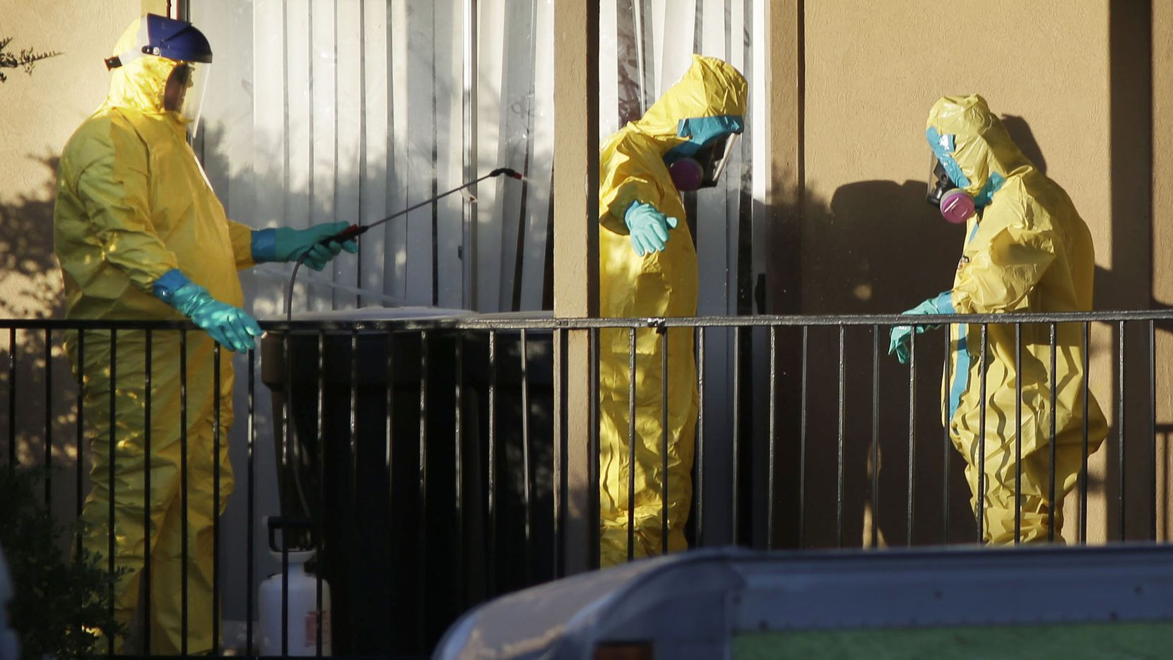 Hazardous material cleaners disinfectant their personal protective equipment after working in the apartment where Thomas Eric Duncan, the Ebola patient who traveled from Liberia to Dallas, stayed last week, Sunday, Oct. 5, 2014, in Dallas. A homeless man being sought because of possible contact with the lone U.S. Ebola patient was found in Texas after several hours of searching, authorities said. (AP Photo/LM Otero)