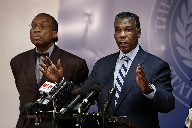 Dallas County Commissioner John Wiley Price (left) listens as Department of Health and Human Services Director Zachary Thompson speaks at a news conference.