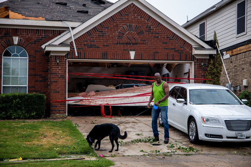 Landon Johnson surveys damages on his neighbor's property with his dog, Titan, after a storm passed through Keller, Texas on Sunday, June 16, 2019.