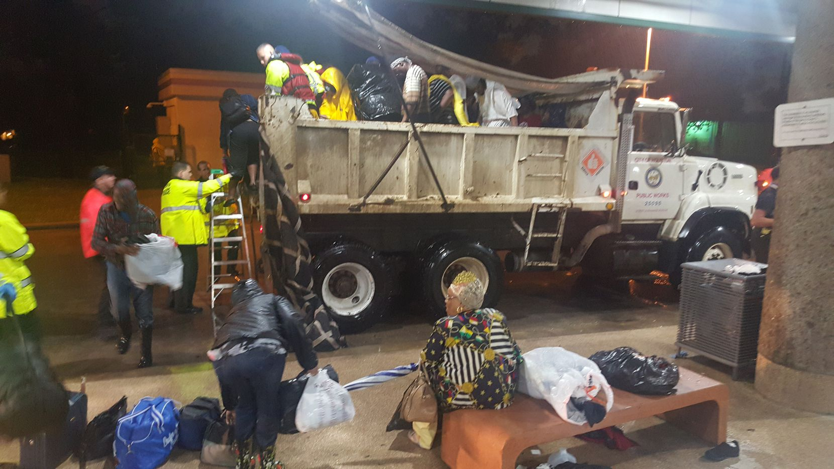 A dump truck pulls into Houston's Kashmere Transit Center with people rescued from Hurricane Harvey around midnight Monday.