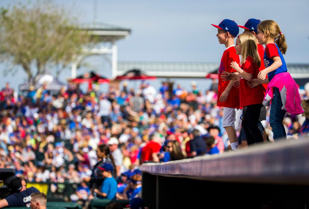 Children dance on top of the Texas Rangers dugout during the fourth inning of a spring training game against the Chicago Cubs at the Rangers' training facility on Sunday, March 5, 2017 in Surprise, Arizona. (Ashley Landis/The Dallas Morning News)