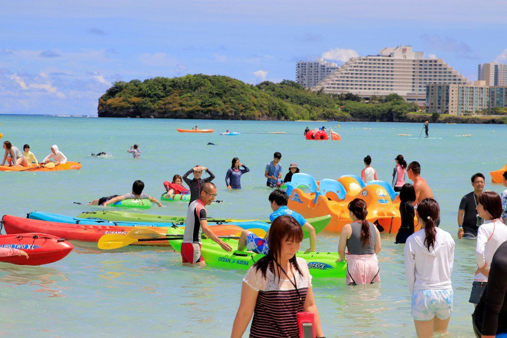 Tourists enjoy the activities along Tumon beach on the island of Guam on August 11, 2017. Tourism-dependent Guam is looking to cash in on its new-found fame as a North Korean missile target, tapping an unlikely promotional opportunity to attract visitors to the idyllic island and prove that all publicity is good publicity.