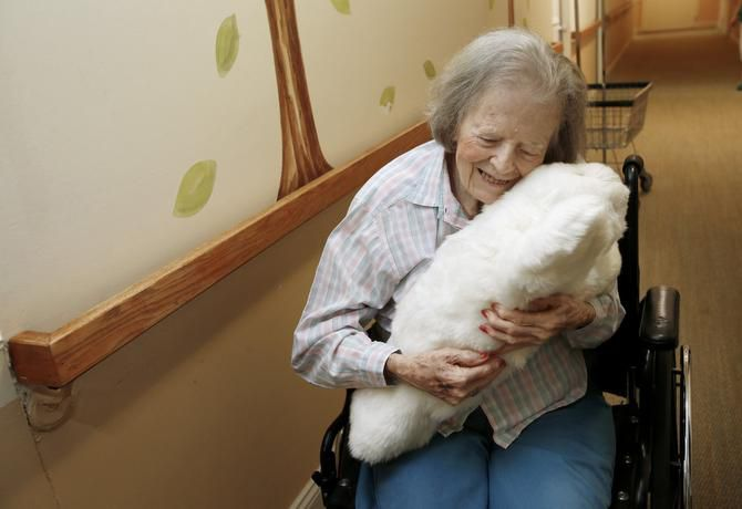 Dorothy Hartley, 89, hugs a robotic pet named Paro at a retirement community in Cupertino, Calif. The Japanese inventor hopes the pet will offer comfort to isolated seniors.