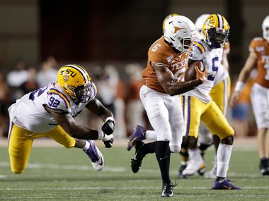 Devin Duvernay #6 of the Texas Longhorns breaks the tackle by Neil Farrell Jr. #92 of the LSU Tigers and runs for a touchdown in the fourth quarter of Texas' 45-38 loss to the Tigers at Darrell K Royal-Texas Memorial Stadium on September 7, 2019 in Austin, Texas.
