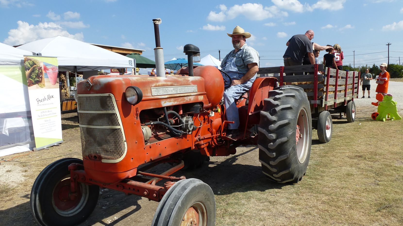 Jake Templin from nearby Anna pulls the hay-ride wagon with a 1958 Allis-Chalmers tractor at Lola's Pumpkin Patch at Lola's Local Market in Melissa. He provides several vintage tractors.