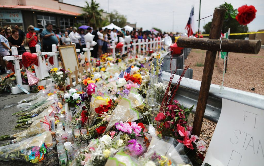 People visited a memorial honoring victims outside Walmart, near the scene of a mass shooting that left 22 people dead, on Aug. 6 in El Paso.  A 21-year-old white man is in custody in El Paso, which sits along the U.S.-Mexico border. President Donald Trump plans to visit the city Aug. 7.