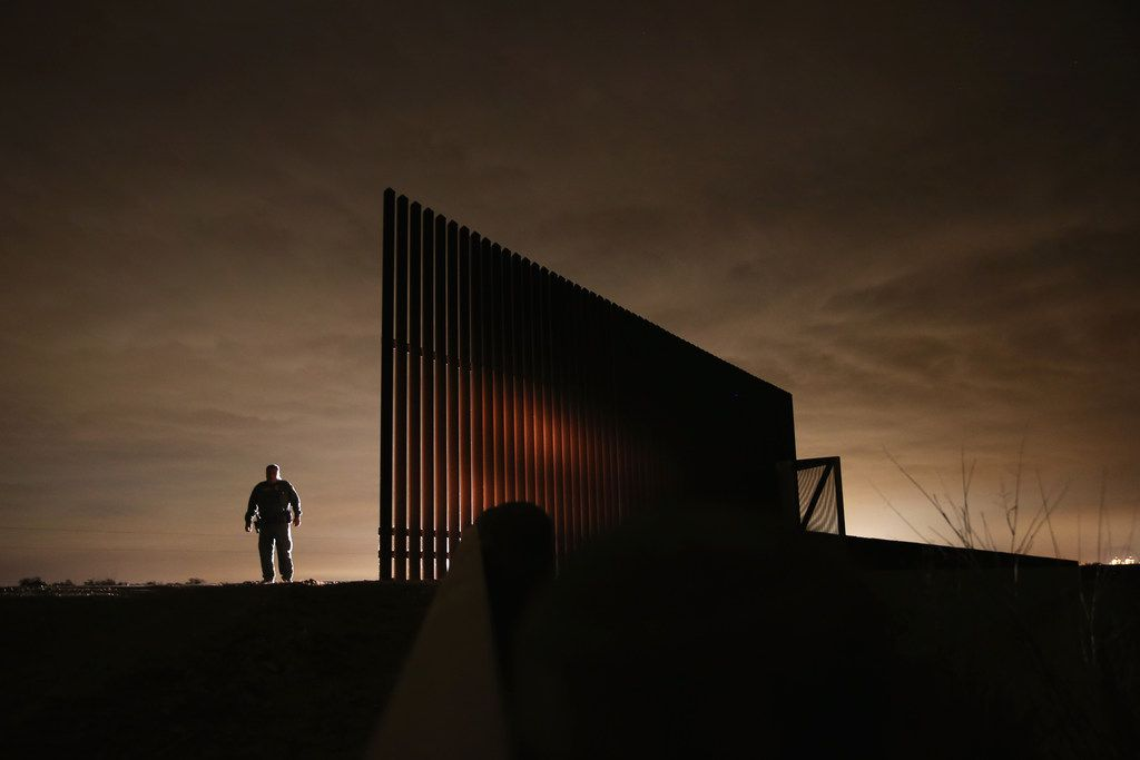 U.S. Border Patrol agent Sal De Leon stands near a section of the U.S.- Mexico border fence while stopping on patrol on April 10, 2013 in La Joya, Texas.