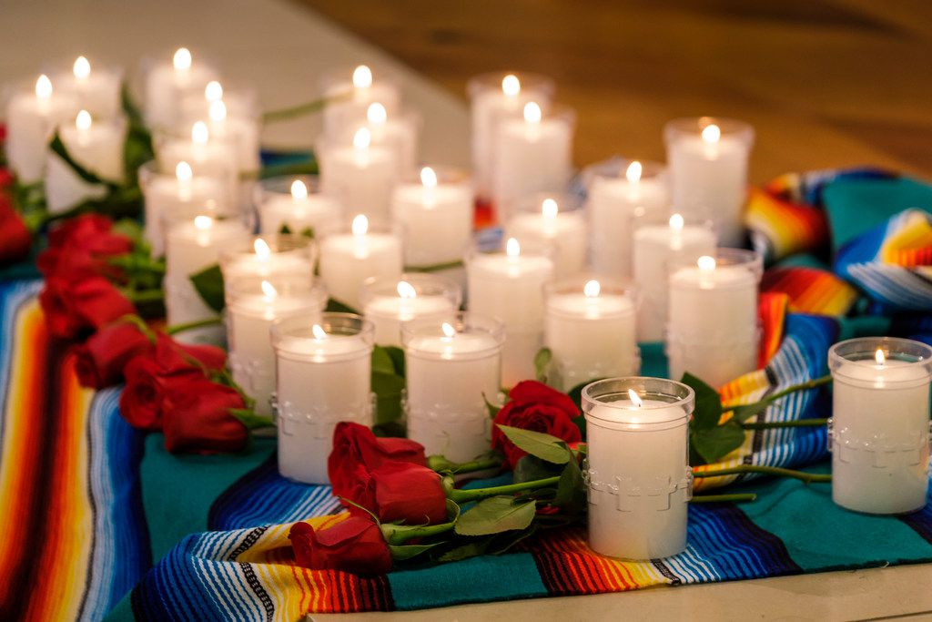 Thirty-one candles and roses, to remember the 31 people killed in two mass shootings, rest at altar during a Mass at the Cathedral Guadalupe to pray for the victims of the shooting violence in El Paso and Dayton, Ohio on Aug. 7 in Dallas.