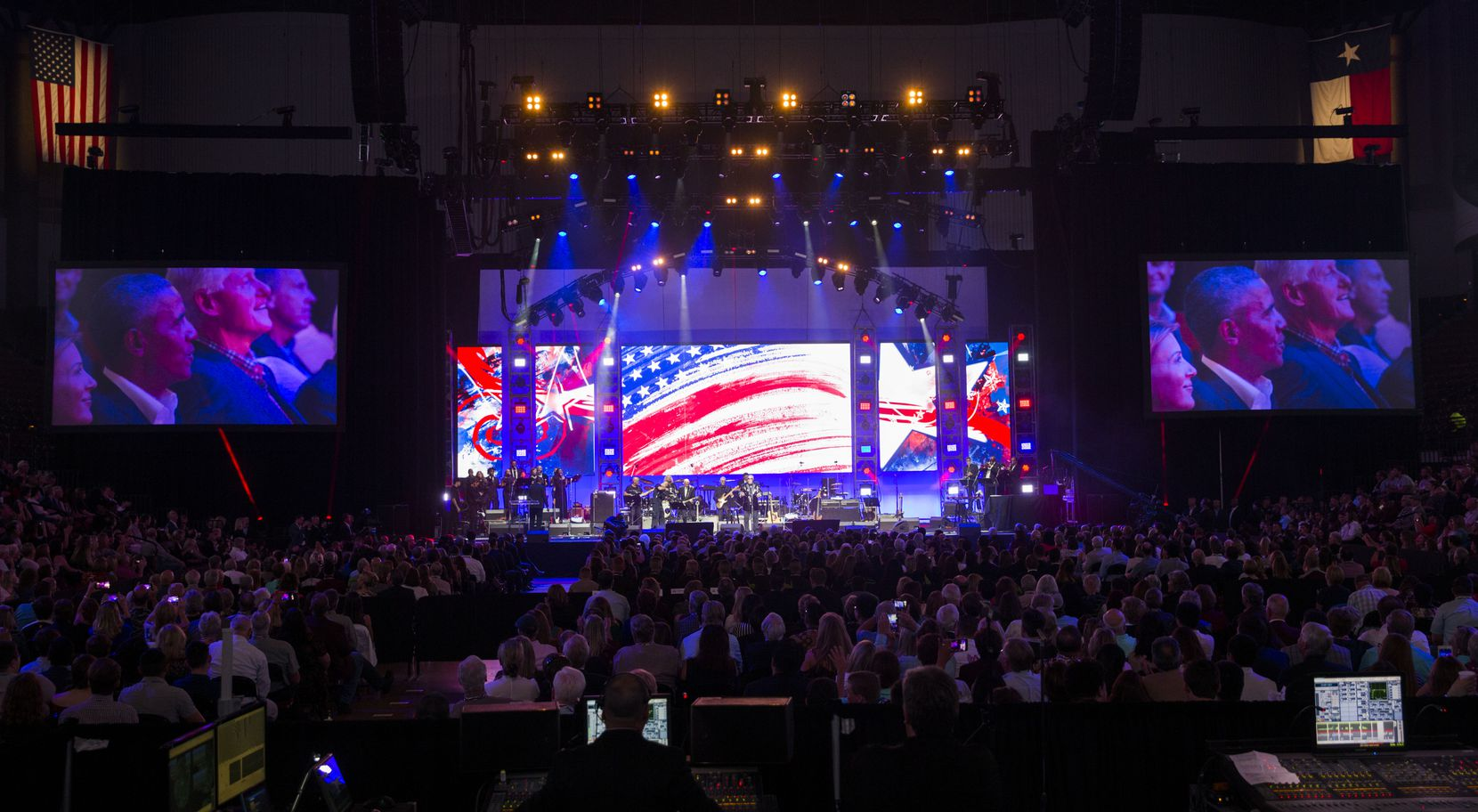 Former presidents Barack Obama and Bill Clinton are shown on video screens as Sam Moore performs during Deep from the Heart: The One America Appeal Concert.
