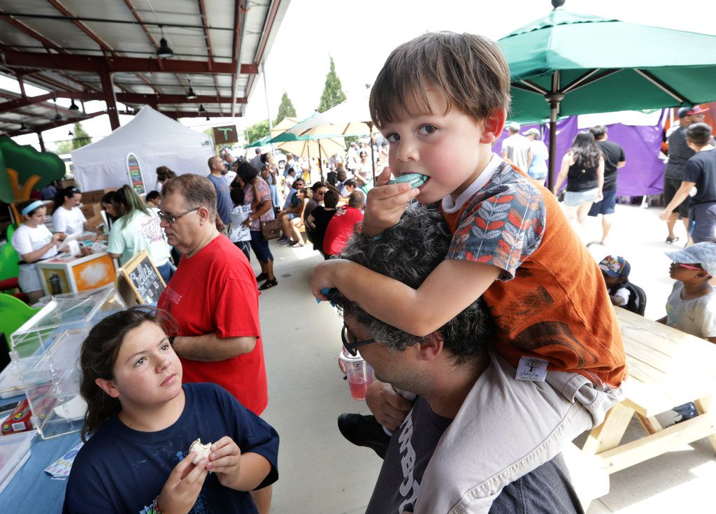 Ten-year-old Zoey Wooten, left, and 4-year-old Rocky Wooten enjoy a macaron with Wayne Wooten during the Frisco Fresh Market in Frisco.