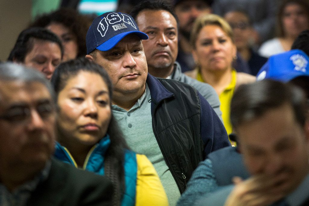 Miguel Hernandez wears a USA hat while listening to Francisco de la Torre, the Mexican consul general in Dallas, address a community meeting on possible deportations at the Consulate General of Mexico on Thursday, Feb. 16, 2017, in Dallas. (Smiley N. Pool/The Dallas Morning News)