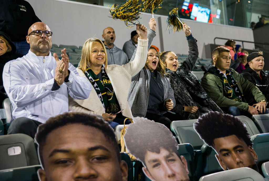 From left, John Earle, Josie Earle, Ali Earle, Alexis Arosemena and Jonathan Arosemena cheer in the stands with cutouts of running back Laderrious Mixon (9), quarterback Stone Earle (3) and wide receiver Carter Self (18) during the first half of a high school football game between Birdville and Fort Worth Boswell on Thursday, November 15, 2018 at the Birdville Fine Arts Center in North Richland Hills, Texas. The Earle family adopted Mixon. (Ashley Landis/The Dallas Morning News)