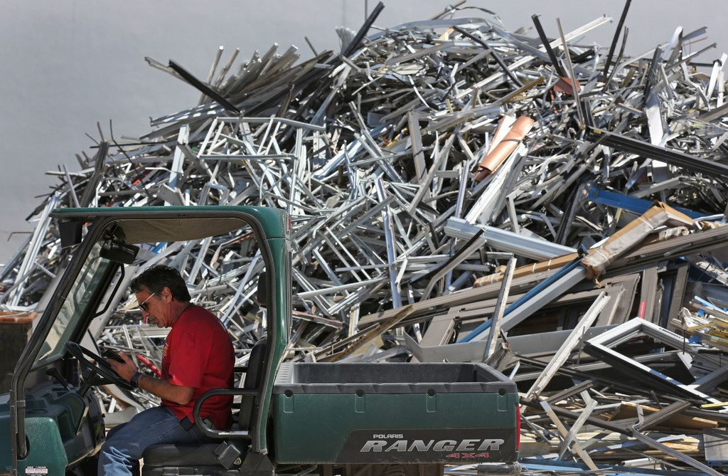 Dennis Laviage of C&D Scrap Metal Recyclers takes a phone call in front of a large pile of aluminum scrap at his business in Houston.