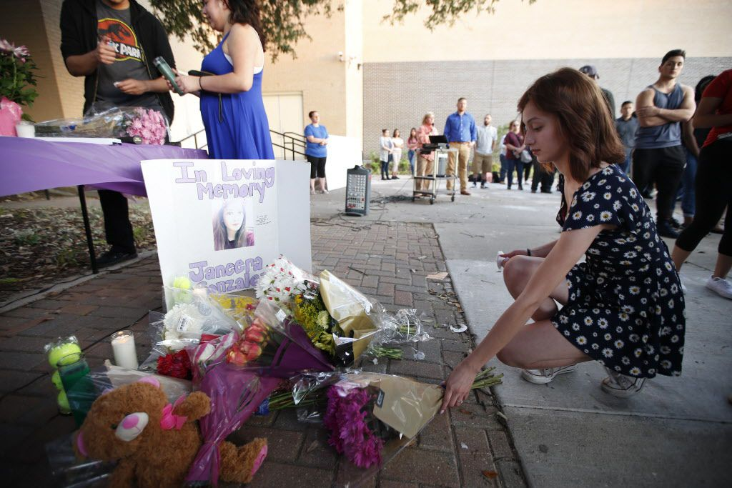 Rosie Atkinson leaves flowers during a memorial held for Janeera Gonzalez, the North Lake College student slain Wednesday, at Irving High School in Irving, Texas on May 8, 2017.