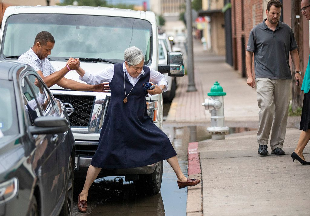 Sister Norma Pimentel gets a hand as she jumps over puddles on the curb in front of the Catholic Charities RGV Humanitarian Respite Center on Tuesday, June 19, 2018, in McAllen.