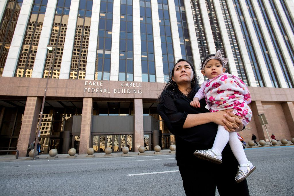Lucia Mejia holds her 19-month-old daughter Teresa outside the Earle Cabell Federal Building and Courthouse before watching video feed of a court hearing for her husband, who is detained by Immigration and Customs Enforcement, Tuesday March 6, 2018 in Dallas.